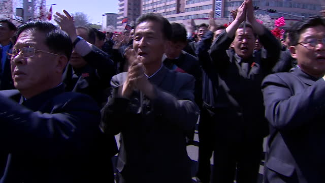 North Korean citizens celebrating the arrival of their leaders Kim JongUn's presence on stage