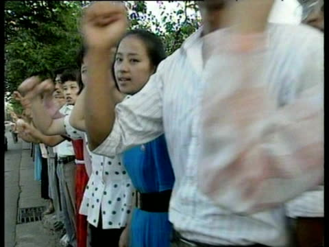 north korean citizens demonstrate and march shaking fists in unison demanding unification of korean peninsula following death of leader kim il sung... - peninsula stock videos & royalty-free footage
