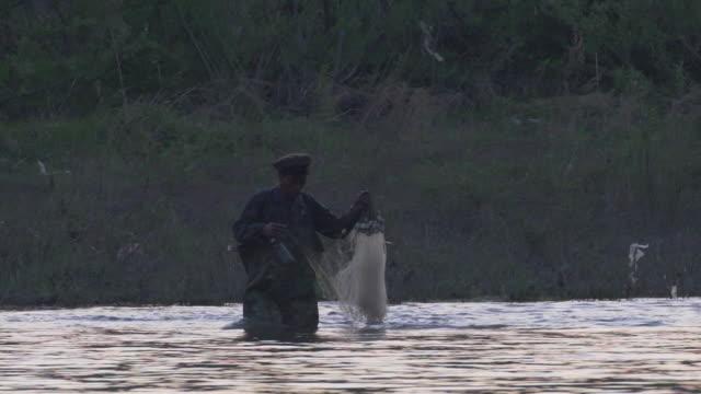 vídeos de stock, filmes e b-roll de a north korean fisherman casting his net in the yalu river - indústria da pesca