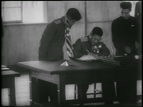 vidéos et rushes de north korean general nam il signing armistice at table as others watch - 1953