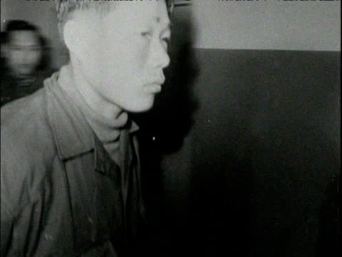 North Korean prisoner is escorted in handcuffs onto stage before press South Korea 24 Jan 68