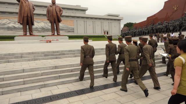 north korean soldiers in pyongyang walking up steps toward mansudae hill grand monument. - norden stock-videos und b-roll-filmmaterial