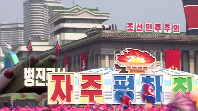 north korean wellwishers wave flowers as they parade through pyonyang with a military inspired carnival float - 行進する点の映像素材/bロール