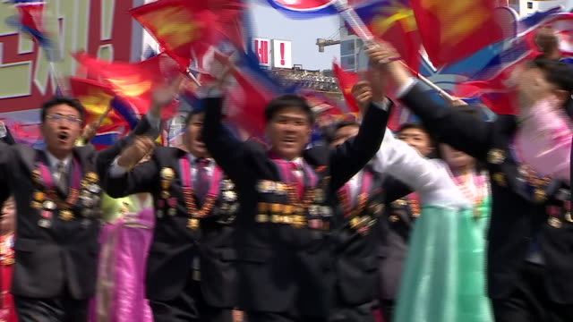 North Korean wellwishers wave flowers as they parade through Pyonyang and past the countries leader Kim Jongun