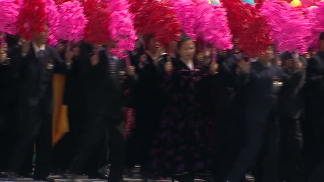 North Korean wellwishers wave flowers as they parade through Pyonyang