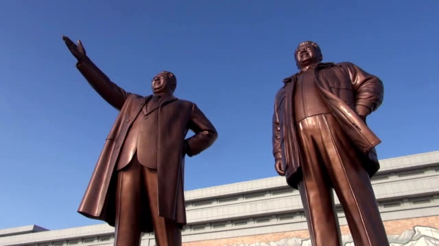 north koreans gathered at mansu hill in pyongyang to offer flowers in front of giant statues of north korean state founder kim il sung and his son... - 像点の映像素材/bロール