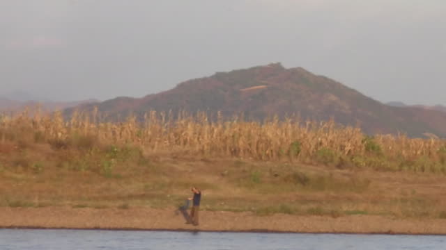 north koreans man washes in the yalu river near the chinese border. - 韓国文化点の映像素材/bロール