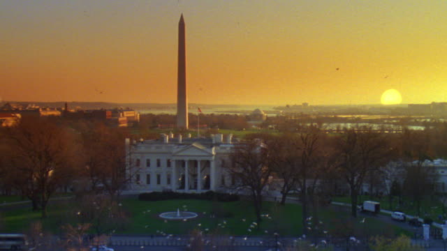 vídeos de stock e filmes b-roll de ms north lawn and white house surrounding terrain at sunrise, sun is above horizon with flock of birds fly around / washington d.c., united states - casa branca washington dc