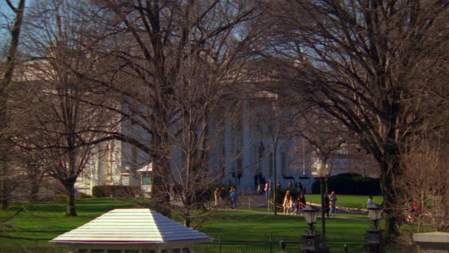 ms north lawn and white house with activity tour group walking down sidewalk / washington d.c., united states - 新古典派点の映像素材/bロール