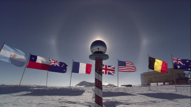 la north pole gazing ball sitting in front of national flags waving in the wind / antarctica - pole stock videos and b-roll footage