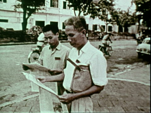 north vietnamese flags hanging outside government building in hanoi north vietnam two vietnamese men standing on street reading newspapers newspaper... - north vietnam stock videos and b-roll footage