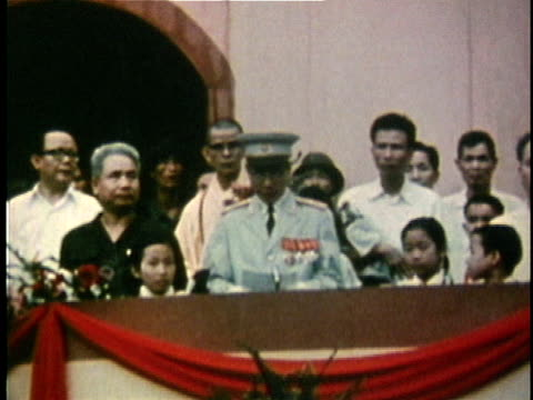North Vietnamese officials standing at podium as crowds rally beneath following the end of the Vietnam War / Vietnam