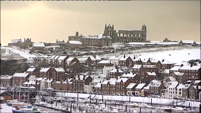 north yorkshire whitby abbey high angle view of river snowcovered rooftops snow on road wide shot of houses with snowcovered roofs cumbria wide shot... - whitby north yorkshire england stock videos & royalty-free footage
