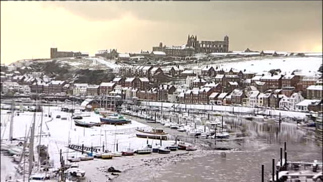 north yorkshire whitby abbey houses with snowcovered roofs pull out icy harbour area and surrounding snow - whitby north yorkshire england stock videos & royalty-free footage