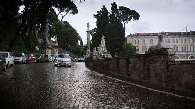 Northeast wet cobble road curving around the Piazza del Popolo