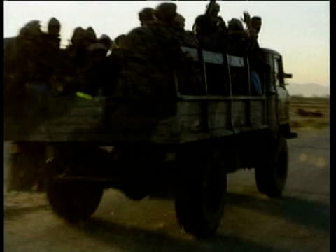 vídeos de stock, filmes e b-roll de northern alliance advances and fires on taliban along road to kabul northern alliance fighters in trucks and tanks canon firing / explosion missiles... - bomb