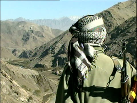 vidéos et rushes de northern alliance soldier holding rifle and surveying scene over bamyan valley war in afghanistan 2001 - guerre d'afghanistan : de 2001 à nos jours