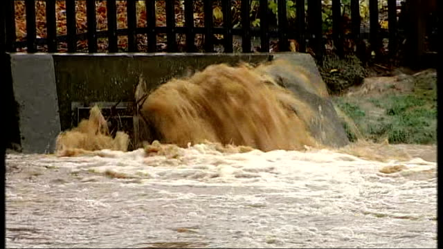 northern england hit by floods and heavy rain; various shots drain overflowing with muddy water high level of running stream of water beneath bridge... - sidewalk gutter stock videos & royalty-free footage