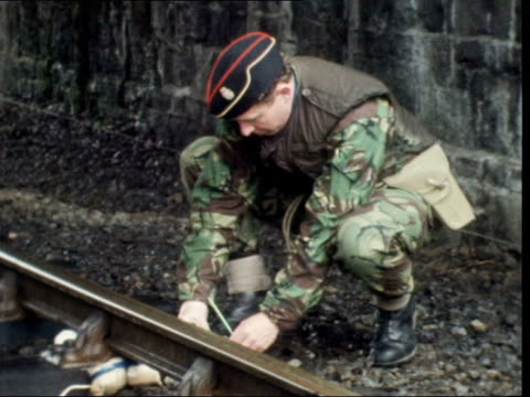 attempt to blow up rail to dublin fails:; northern ireland: county armagh: silverwood: ext rail: soldier on duty zoom into charges: pan right to army... - ulster county stock videos & royalty-free footage