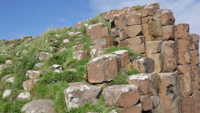 northern ireland basalt columns between grassy heights at giants causeway.mov - mythologie stock-videos und b-roll-filmmaterial