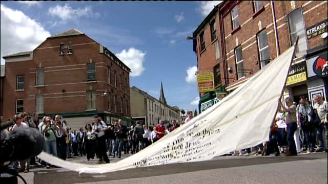 bloody sunday killings saville report exonerates bloody sunday victims williams street crowd raising paper banner depicting front page of widgery... - saville report stock videos & royalty-free footage
