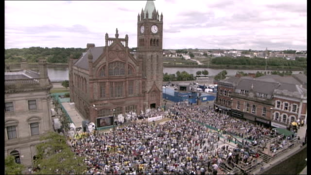 bloody sunday killings saville report exonerates bloody sunday victims general view of massed crowd cheering in guildhall square sot - saville report stock videos & royalty-free footage