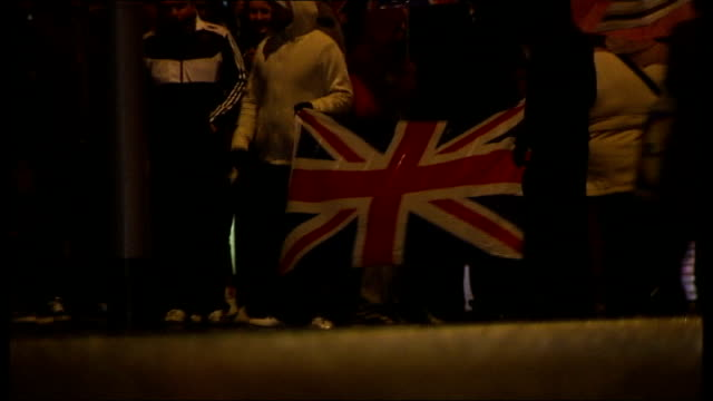 16 police officers injured in clashes protesters wearing balaclavas and hoodies standing in street low angle view protesters with union jack flag... - itv weekend lunchtime news点の映像素材/bロール