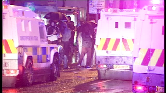 flag protests police and political leaders meet to try to end rioting northern ireland belfast line of riot police walking along street as burning... - 乗り物の明かり点の映像素材/bロール