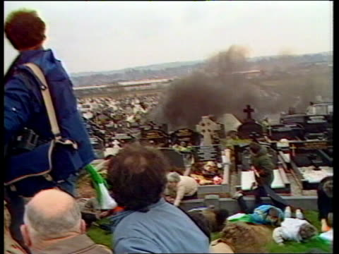 funeral grenade attack: man charged; tx 16.3.88 itn northern ireland: belfast: milltown cemetary: tms mourners standing on bank, graves in b/g as... - cemetery stock videos & royalty-free footage