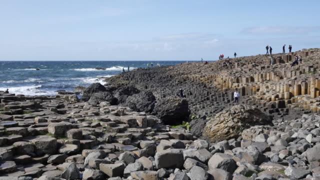 vídeos y material grabado en eventos de stock de northern ireland giants causeway hexagonal stones and tourists in distance - provincia de ulster
