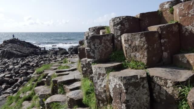 vídeos de stock, filmes e b-roll de northern ireland giants causeway hexagonal stones dominate foreground - província de ulster