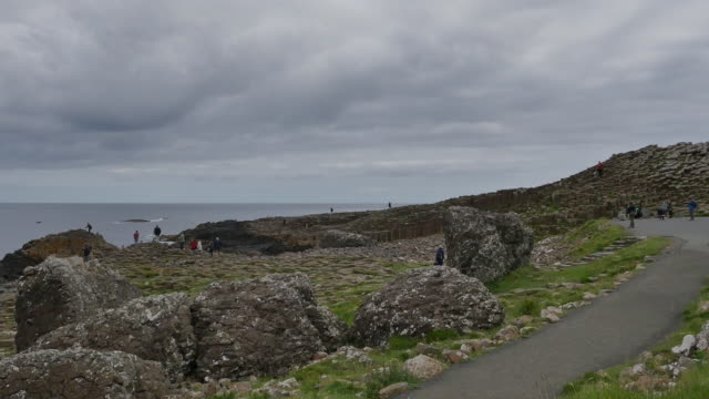 northern ireland giants causeway path under dark cloud - igneous stock videos & royalty-free footage