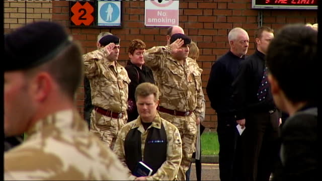 hearses depart massereene barracks soldiers lined up next to floral tributes and saluting as hearses containing union jack drpaed coffins leaves... - hearse stock videos & royalty-free footage