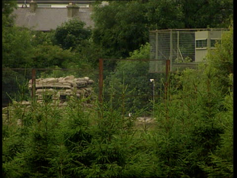 vídeos de stock e filmes b-roll de mortar attack on security base / gerry adams hints at ceasefire anat ireland south armagh newtonhamilton security base ext gv rooftops of security... - tom bradby