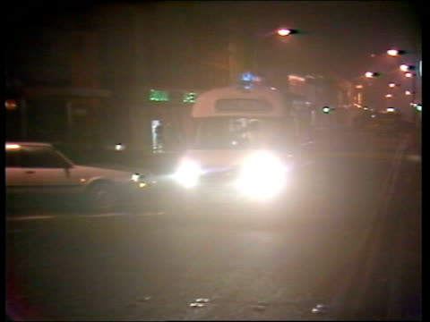 vidéos et rushes de newry mortar attack; northern ireland: co down: newry: ext / night landrover with headlights along street towards and past l-r to bv ambulance along... - irlande du nord