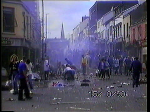 omagh bombing: arrests made; lib northern ireland: omagh: people milling about in street and helping others in aftermath of bomb tx 21.9.98/c4n - bomb stock videos & royalty-free footage