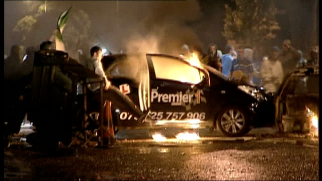 over eighty police officers injured during riots in belfast; 12.7.2010 ext / night rioters setting fire to learner driver car armoured police... - water cannon stock videos & royalty-free footage