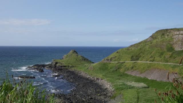 northern ireland path along the causeway coast pan and zoom - mythologie stock-videos und b-roll-filmmaterial