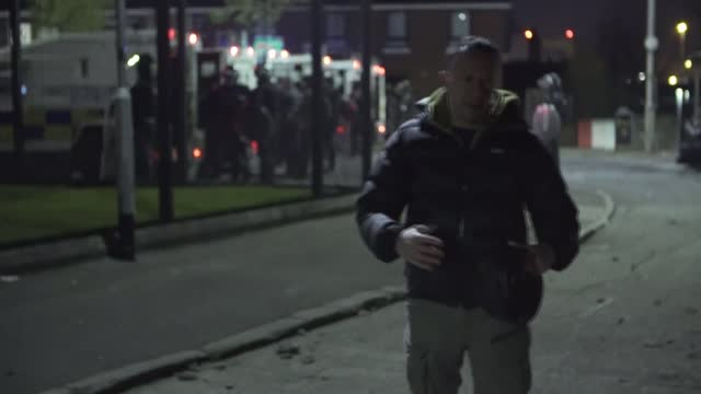 petrol bombs thrown at police as rioting continues; northern ireland: belfast: ext / night riot police officer along with dog various of rioters... - war and conflict stock-videos und b-roll-filmmaterial