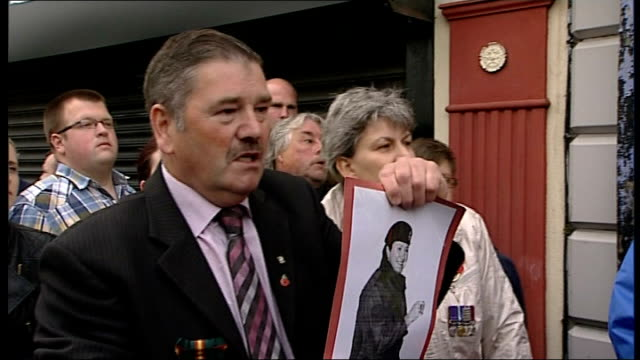 republican parade in county tyrone: kelly interview/parade general views; police officers on the street as man holds up photograph of woman wearing... - northern ireland stock videos & royalty-free footage