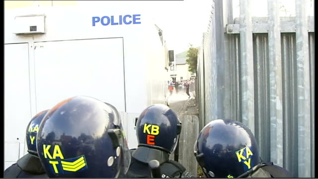 second night of rioting over orange order march route northern ireland belfast ext riot police gathered as bottles fly overhead / wide shot of police... - hose stock videos & royalty-free footage