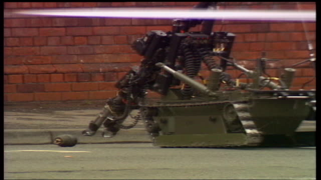 stockvideo's en b-roll-footage met utv northern ireland troubles footage clipreel 43 bomb disposal robot positioned in road by grenade on ground nudging it along - bom