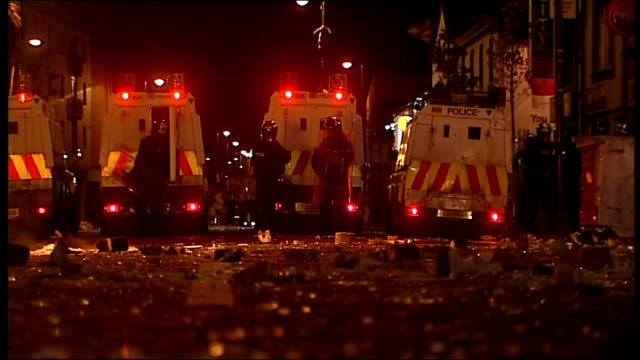 Violence continues in Belfast despite plea from Hillary Clinton EXT / NIGHT Low Angle shot of line of police armoured vehicles forming barricade...