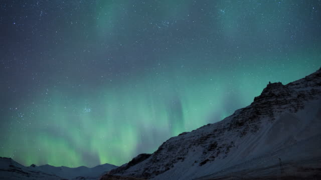Northern lights dancing over the mountains of southern Iceland