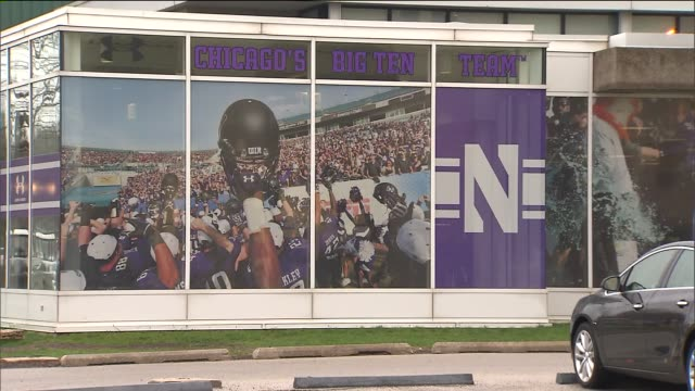 wgn northwestern university's football team logo hangs on campus buildings and outside the welshryan arena as dozens of northwestern football players... - ncaa college football stock videos and b-roll footage