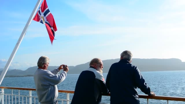 stockvideo's en b-roll-footage met norway cruise hurtigruten ship back deck with passengers out enjoying scenes near the arctic circle crossing with old classic norway postal flag - retirement
