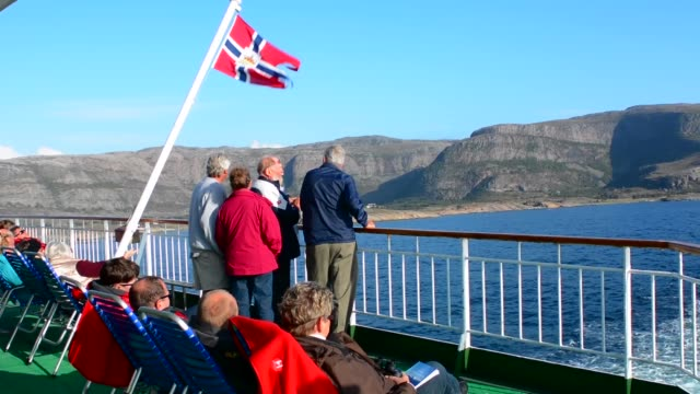 norway cruise hurtigruten ship back deck with passengers out enjoying scenes near the arctic circle crossing with old classic norway postal flag - passagier wasserfahrzeug stock-videos und b-roll-filmmaterial