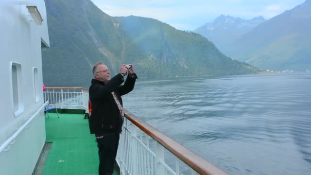 Norway cruise Hurtigruten ship fjord man taking photo of scenic  Hjorundjorden from balcony