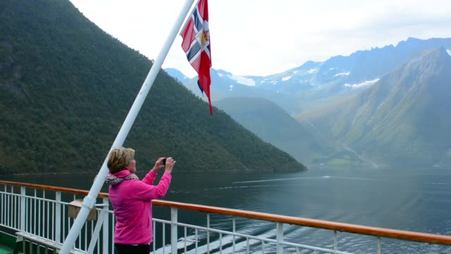 norway cruise hurtigruten ship fjord woman taking photo of scenic from balcony with old norway postal flag in hjorundjorden - norway stock videos & royalty-free footage