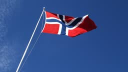 Norway flag flapping in wind on blue sky.